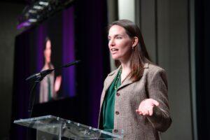 Sarah Low speaking at a podium